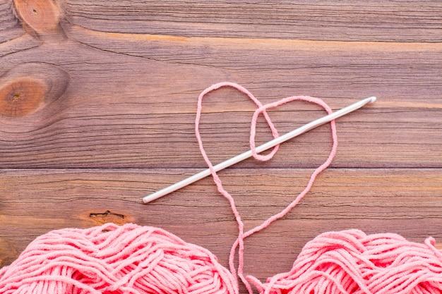 Coração de fio rosa, emaranhado de fios e agulha em uma mesa de madeira.