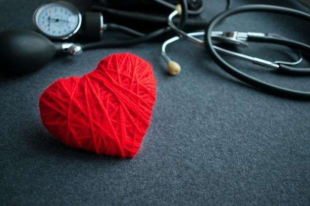 Coração de fio vermelho com tonometer na mesa cinza
