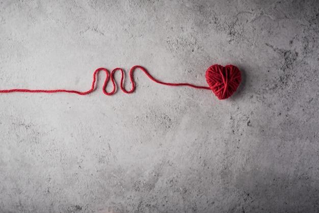 Coração de fio vermelho em forma no fundo da parede