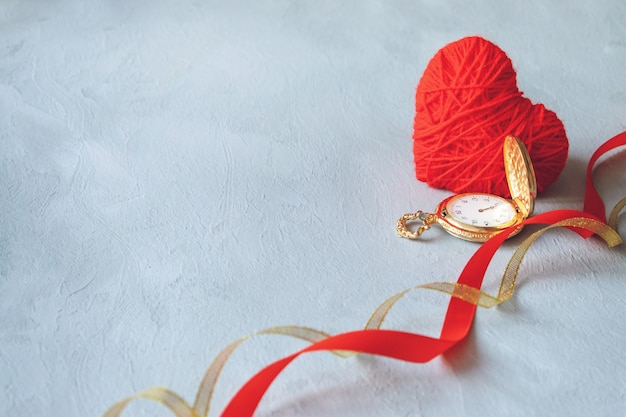 Coração de fio vermelho, relógio de bolso de ouro