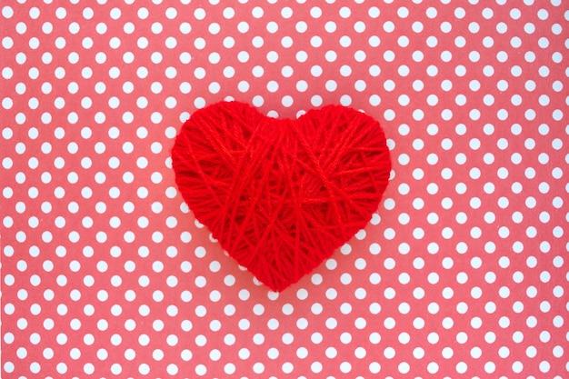 Coração de fio vermelho sobre fundo de bolinhas têxtil