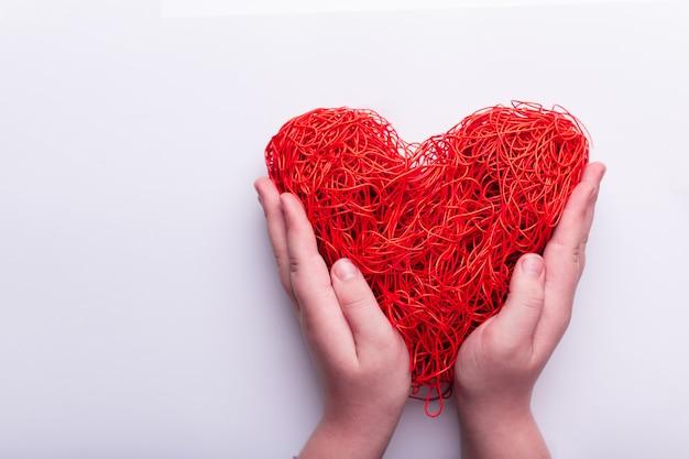 Coração de fios emaranhados vermelhos. mãos seguram o coração. conceito dia dos namorados. vista de cima