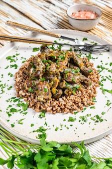Coração de frango, fígado e estômago grelhados com trigo sarraceno em um prato.