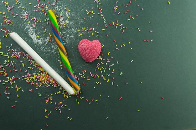 Coração de geléia perto de bastões de doces