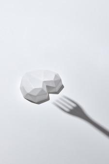 Coração de gesso branco e sombras duras do garfo