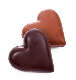 Coração de grãos de café com doces em forma de coração em fundo branco.