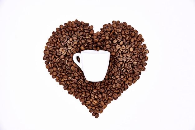 Coração de grãos de café e uma xícara branca.