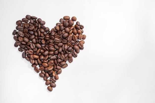 Coração de grãos de café isolado no branco