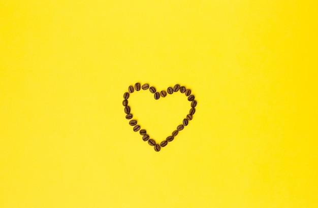 Coração de grãos de café sobre fundo amarelo. conceito criativo de comida mínima.
