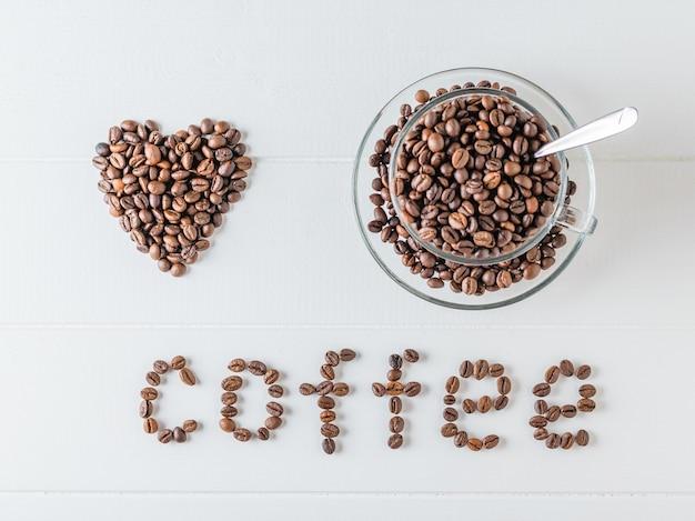 Coração de grãos de café, xícara de café em grão e café inscrição na mesa de madeira branca. a vista do topo. grãos para a preparação da bebida popular.