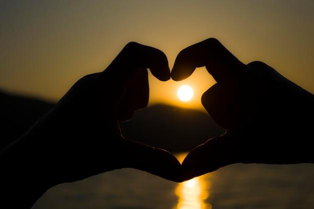 Coração de handsevening pôr do sol atrás da montanha em um grande lago vista romântica do pôr do sol na ...