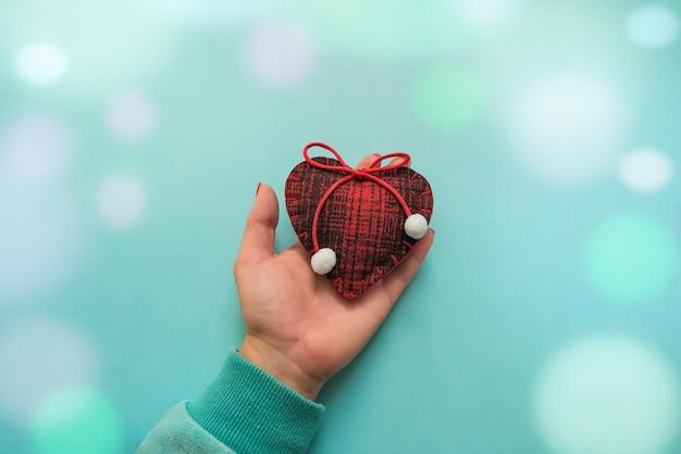 Coração de lã na mão. conceito de dia dos namorados, bokeh.