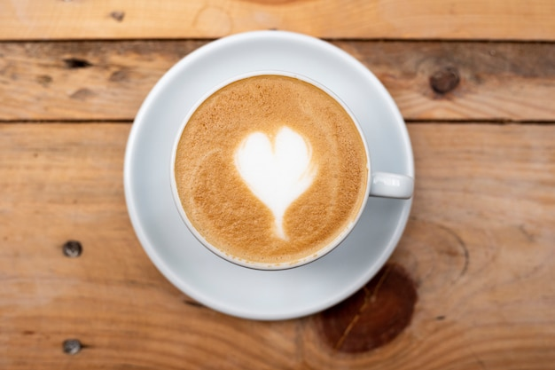Coração de latte art na mesa de madeira
