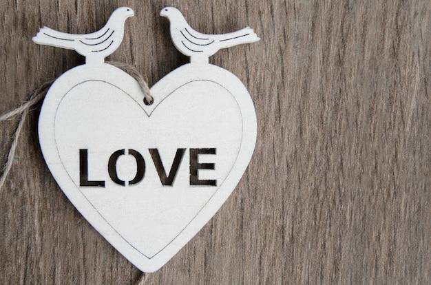 Coração de madeira branca com dois pombos na parte superior. decoração de cartão de felicitações