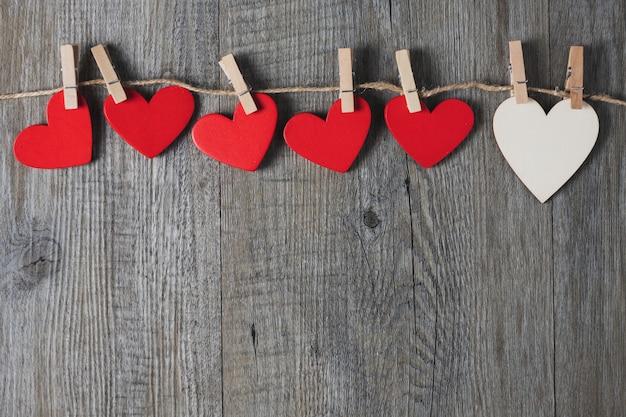 Coração de madeira branco e vermelho colocado em um cinza de madeira, vista superior, tema do dia dos namorados