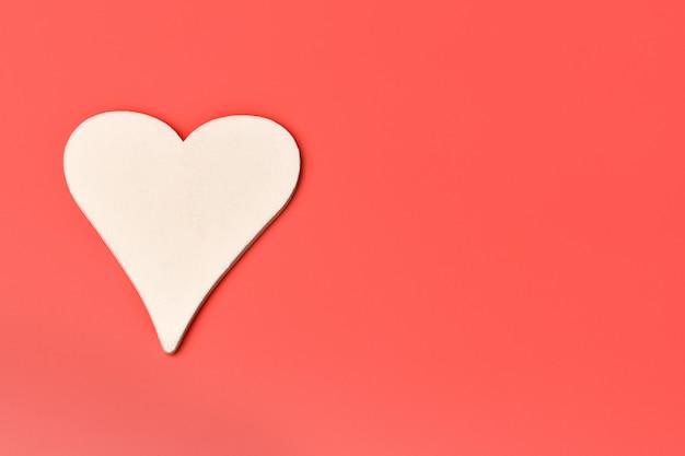 Coração de madeira branco em um vermelho. dia dos namorados, 14 de fevereiro.