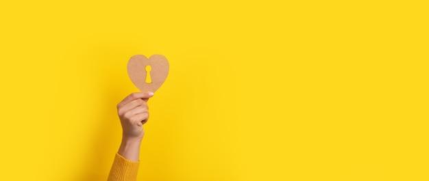 Coração de madeira com fechadura na mão sobre fundo amarelo, imagem panorâmica