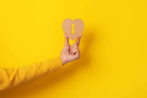 Coração de madeira com fechadura na mão sobre fundo amarelo