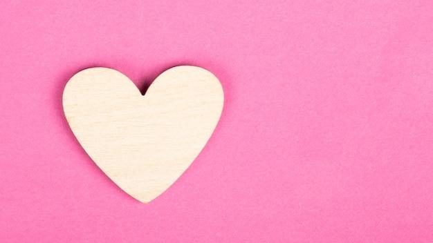 Coração de madeira dos namorados em fundo rosa com espaço de cópia