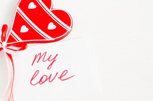 Coração de madeira e notas meu amor na mesa rústica de luz.