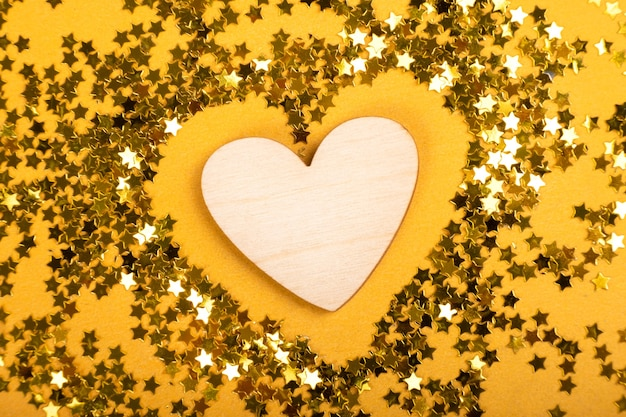 Coração de madeira em estrelas douradas sobre fundo amarelo valentine day 14 de fevereiro, dia mundial do coração 29 de setembro.
