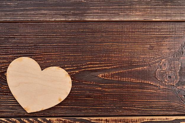 Coração de madeira em plano de fundo texturizado escuro.