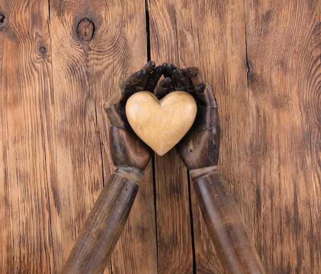 Coração de madeira nas mãos de um manequim