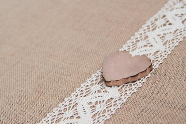 Coração de madeira no laço na serapilheira perto com espaço de cópia