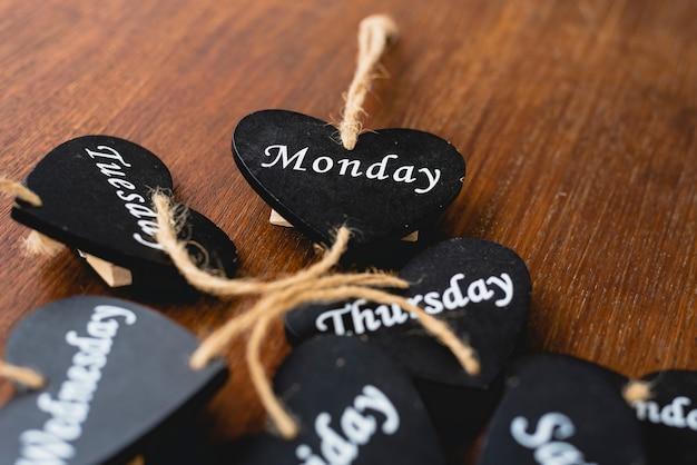 Coração de madeira preta com dias do fim de semana escrito nele.