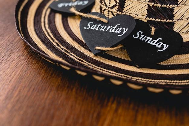 Coração de madeira preto, dias de fim de semana sobre um chapéu mexicano.