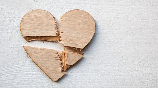Coração de madeira quebrada na mesa de madeira.