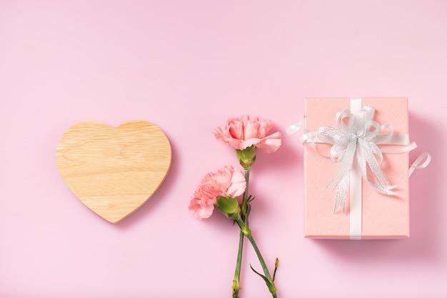 Coração de madeira vazio para mensagem com caixa de presente e flores de cravo, dia das mães e dia dos namorados
