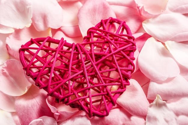 Coração de madeira vermelho decorativo feito de rattan com pétalas de rosa cor de rosa. foco seletivo.