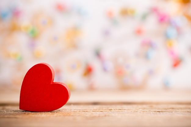 Coração de madeira vermelho em um fundo de madeira com fundo de boke