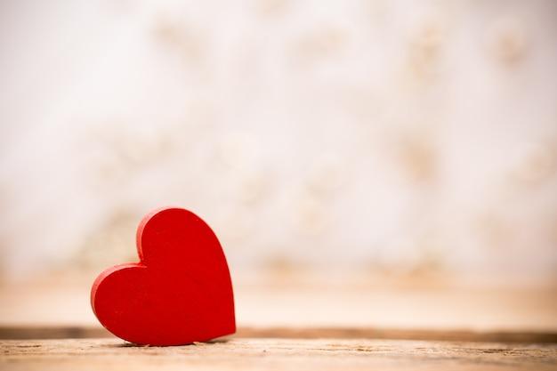 Coração de madeira vermelho sobre um fundo de madeira com fundo de boke.