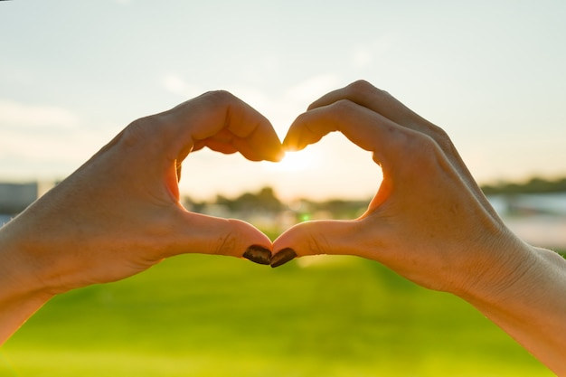 Coração de mãos femininas, grama verde céu noite sol fundo