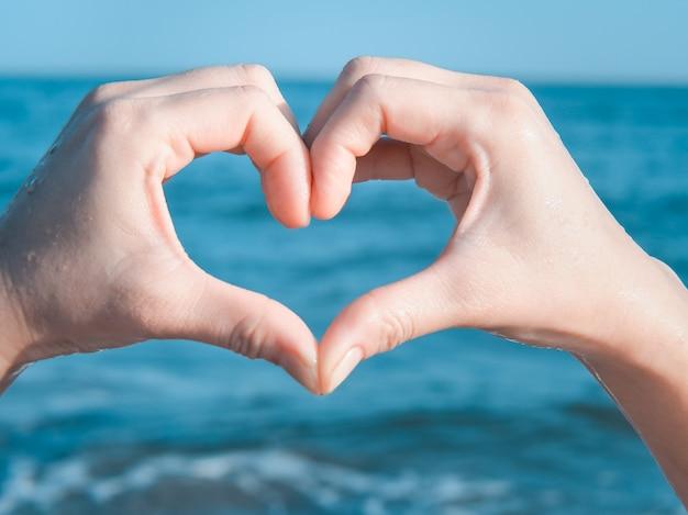 Coração de mãos na praia Foto Premium