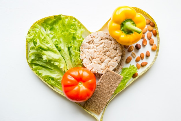 Coração de medir a fita com legumes nozes e frutas conceito dieta