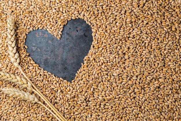 Coração de metal cinza de sementes de trigo dourado maduro