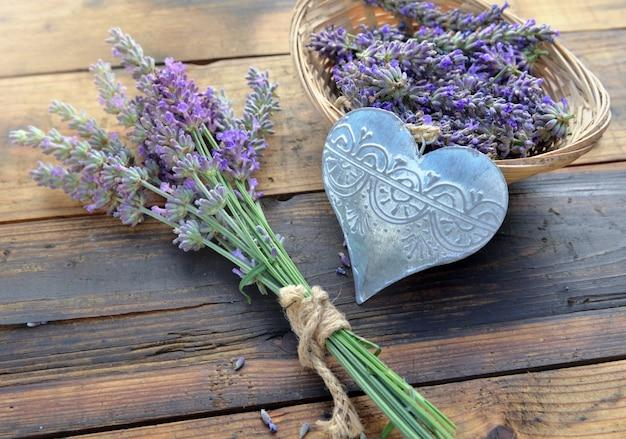 Coração de metal decorativo entre flores de lavanda em fundo de madeira