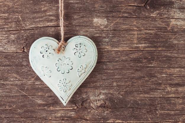 Coração de metal no antigo fundo de madeira