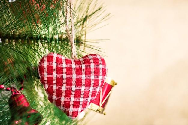 Coração de natal pendurado na árvore de natal em fundo dourado