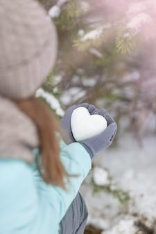 Coração de neve nas mãos de uma garota