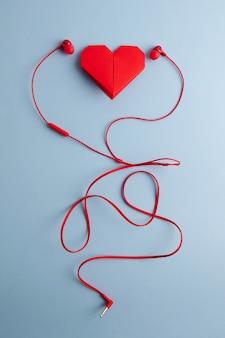 Coração de origami vermelho com fones de ouvido na mesa azul