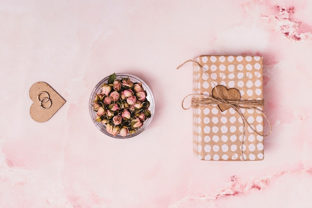 Coração de ornamento com anéis perto de flores em lata e caixa de presente