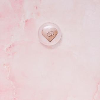 Coração de ornamento com anéis sob o vidro