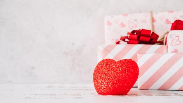 Coração de ornamento perto de caixas de presentes