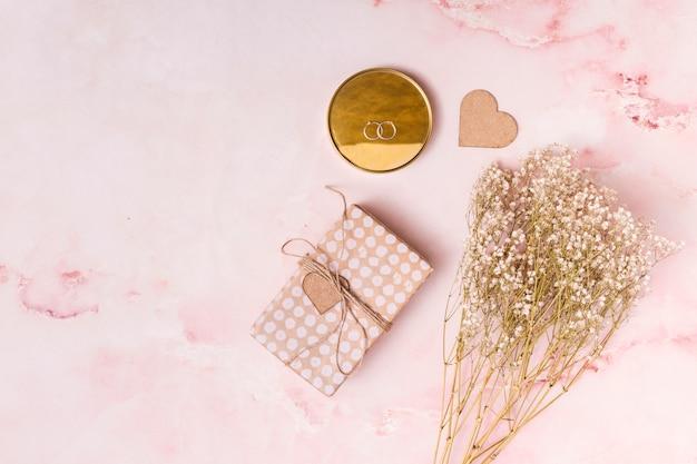 Coração de ornamento perto de monte de flores, caixa de presente e anéis na rodada