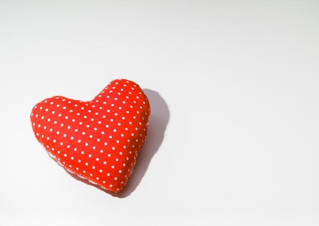 Coração de pano vermelho sobre uma mesa branca.