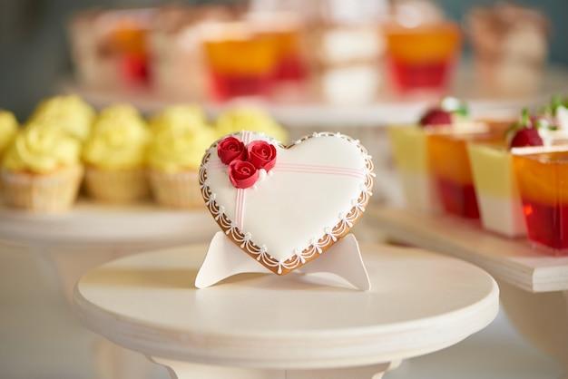 Coração de pão de mel vitrificado fica em um suporte de madeira no restaurante. está decorado com rosas vermelhas doces e um pequeno padrão. há uma barra de chocolate colorida com cupcakes e geléias atrás dela.